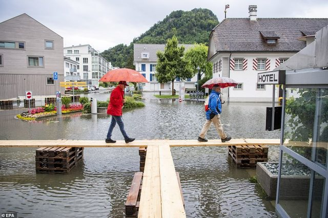 SWITZERLAND: The village square of Stansstad, near the city of Lucerne, is seen underwater with residents forced to walk across raised platforms after heavy rain hit Europe
