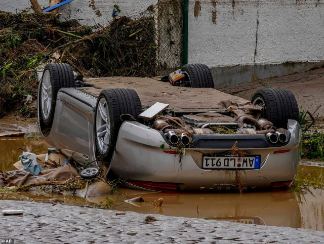 A car rests on its roof after being swept away in floodwaters at Insul, on the banks of the Ahr river, Germany