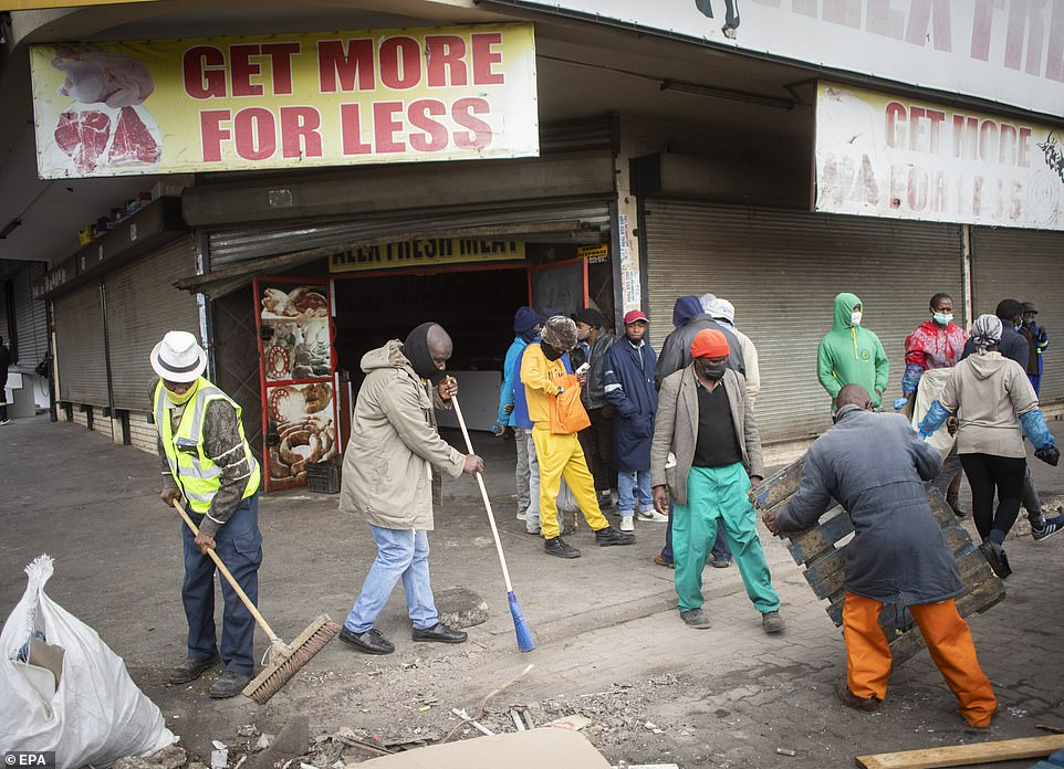 Residents clean up the streets and help local businesses after days of looting in Alexandra township, Johannesburg, this week