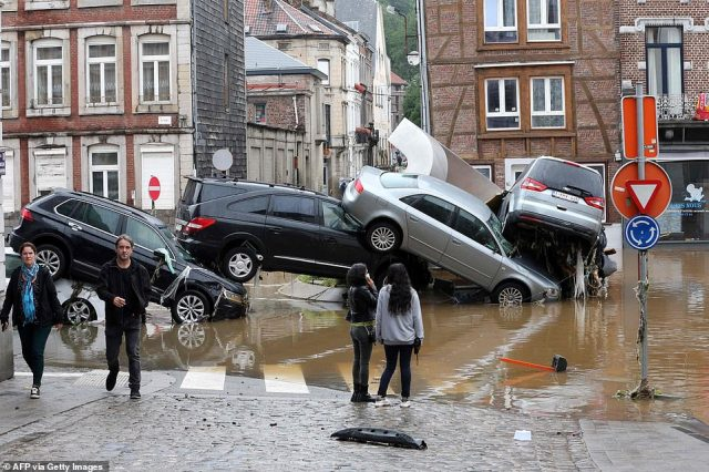 Stunned onlookers are confronted by an impossible-seeming pile of cars that washed together in Verviers, Belgium, after heavy flooding hit the area overnight