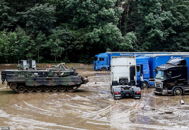 German army armoured vehicle pulls a truck from the mud after flooding in Hagen, Germany