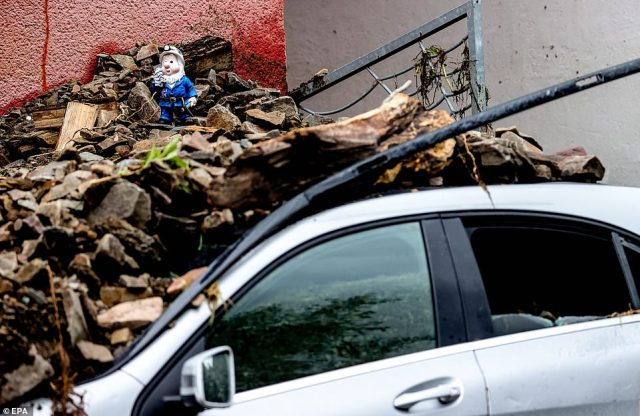 A gnome is seen perched on top of a pile of debris after it buried a car in Hagen, western Germany, overnight