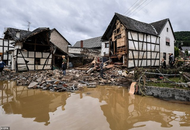 Local residents inspect collapsed houses after heavy flooding of the river Ahr, in Schuld, Germany