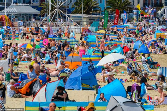 The beach is packed as families and sunbathers flock to the seaside resort of Weymouth in Dorset