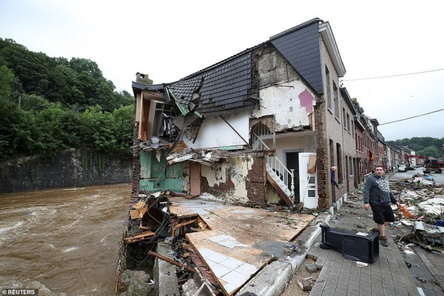 A partially-destroyed house sits beside the La Vesdre river in Verviers, Belgium, after it broke its banks and swept away part of the building
