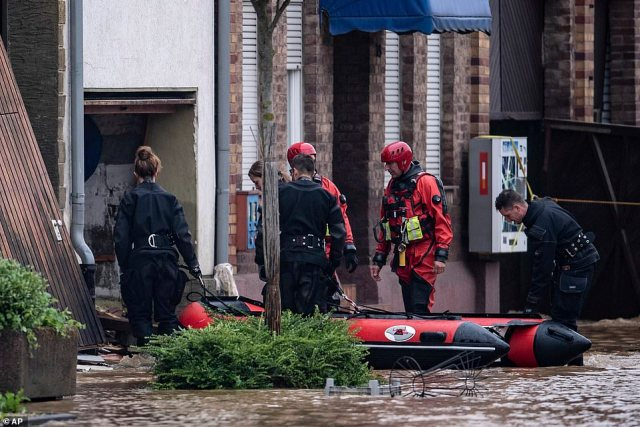Lifeguards and police divers with an inflatable boat go into a flooded home in Erftstadt, Germany, as they search for victims
