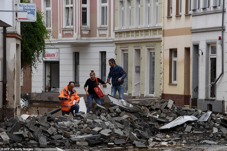 People climb over rubble piled up in a street after the floods caused major damage in Bad Neuenahr-Ahrweiler