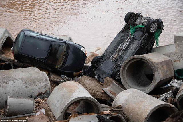 Two cars lie at the bottom of a deep hole created when waterlogged ground collapsed into a nearby gravel pit in Germany