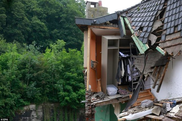 Clothes are seen hanging from the partially-destroyed wardrobe of a house in Verviers, Belgium