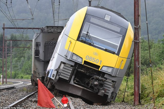 A railway carriage of the Belgium SNCB train service is derailed following heavy rains and floods in Rochefort