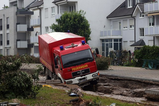 A view of a vehicle of the fire department (Feuerwehr) stuck in a damaged street of a residential area after flooding in Bad Neuenahr-Ahrweiler, Germany