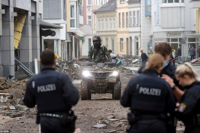 Police officers inspect the area as a person rides a quad bike amid the debris after flooding in Bad Neuenahr-Ahrweiler