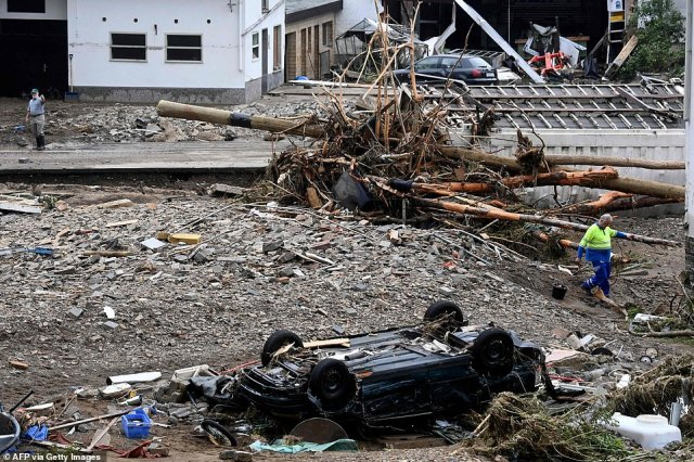 Men walk past driftwood, rubble, and an overturned car, as they survey the damage caused by severe floods in Schuld near Bad Neuenahr-Ahrweiler