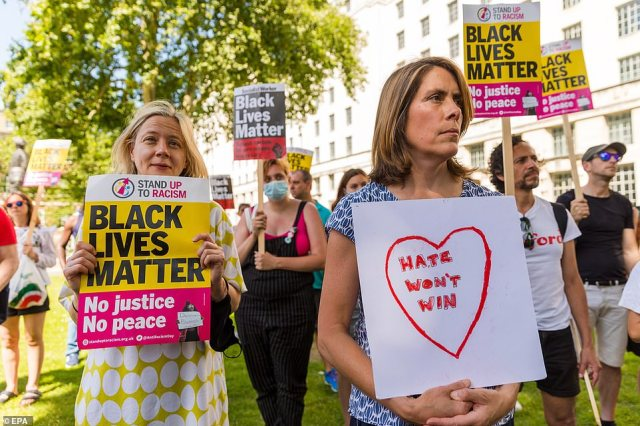 Demonstrators from Stand Up To Racism stage a protest outside Downing Street this afternoon as they hold placards