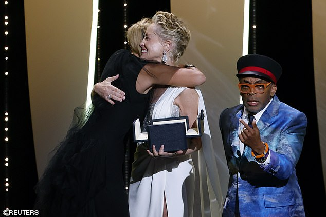Chaos: The director also embraced actress Sharon Stone as she accepted the prize, while Spike continued to look sheepish behind them