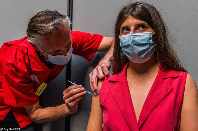 A woman receives a Covid vaccine at a pop-up centre in the Tate Modern's Turbine Hall to protect herself against the virus
