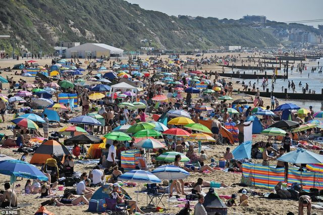 Tourists sit on Bournemouth beach and enjoy the rising mercury levels as the nation enjoys spells of warm sunshine