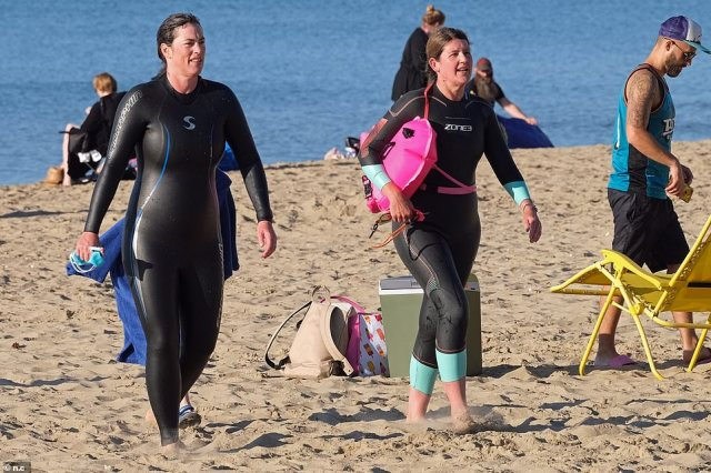 People walk along Branksome beach in Poole in their swimming gear as the region enjoys a warm spell of sunshine