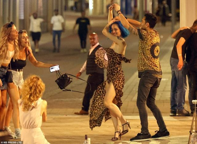 People dance in the streets as they enjoy a night out in Leeds on Saturday as a blast of warm air coming in from the Azores in the North Atlantic brings with it sizzling heat