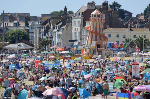 Crowds of visitors pack onto the beach in Weymouth today as the UK enjoy a heatwave after a week of rain and thunderstorms
