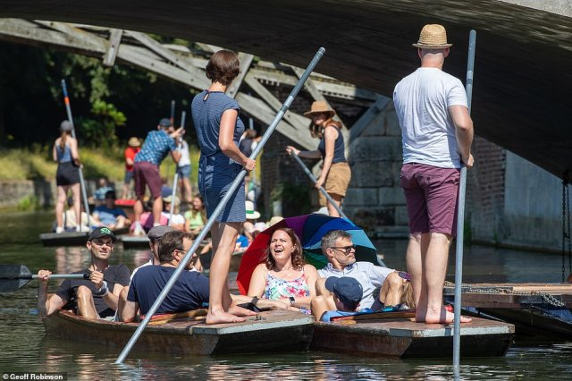 A group of friends enjoy the sizzling heat as they go out punting on a busy River Cam in Cambridge today