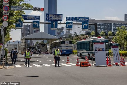 Guards block a road leading into the Tokyo Olympics athletes' village on July 19 after two South African football players tested positive for COVID-19 inside