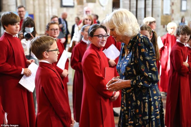 Camilla looked stylish in a navy blue dress adorned with colourful feathers, teamed with tan court shoes as she spoke to members of the choir