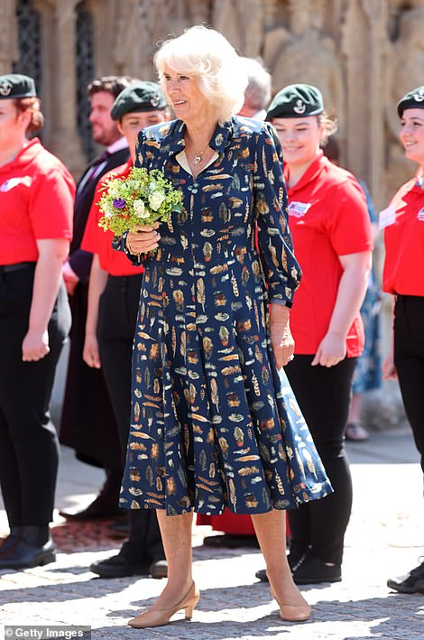 The Duchess of Cornwall clutches her posy of flowers, given to her by members of the choir, as she departs Exeter Cathedral today