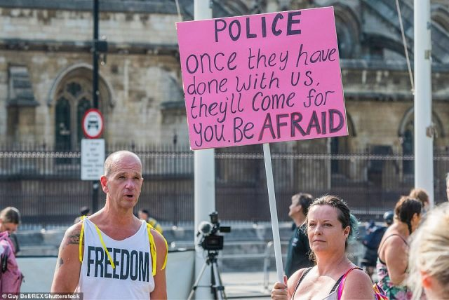 Activists hold signs with anti-vaccination and anti-police messages in Westminster today