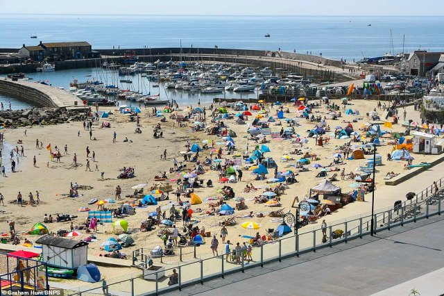 Sunworshippers flocked to the beach today as the temperature hits 32C in Lyme Regis, Dorset