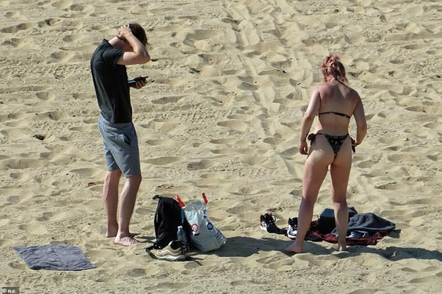 A couple set up camp on a sunny and sandy Bournemouth beach on the hottest day of the year so far