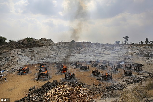 Pictured: Funeral pyres of twenty-five COVID-19 victims burn at an open crematorium set up at a granite quarry on the outskirts of Bengaluru, India, May 5, 2021
