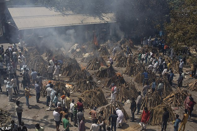 Pictured: Multiple funeral pyres of those who died of COVID-19 burn at a ground that has been converted into a crematorium, April 24, 2021. India's coronavirus death toll is up to 10 times higher than the nearly 415,000 fatalities reported by authorities, a new study has claimed