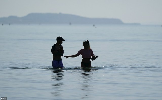 Two people wade into the sea as they savour the glorious British summer weather at Bournemouth Beach on Tuesday, July 20