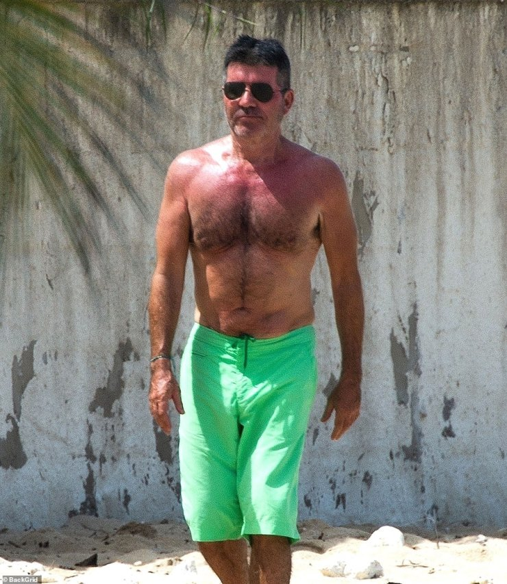 On the mend:Continuing his remarkable recovery since breaking his back, Simon went shirtless in a pair of green swimming shorts as he headed down to the ocean for the walk