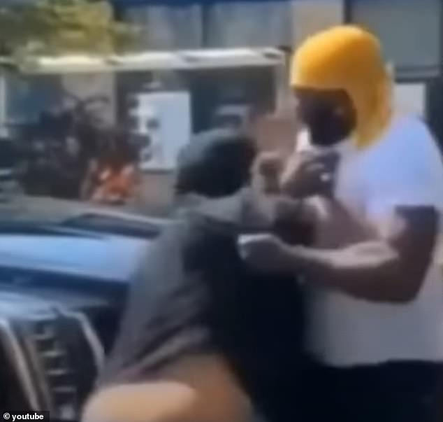 The 34-year-old fan (pictured in the white shirt) was filmed wrestling briefly with Tekashi 6ix9ine's bodyguards after they allegedly chased him for 20 blocks in New York and smashed his phone for filming the rapper in August last year