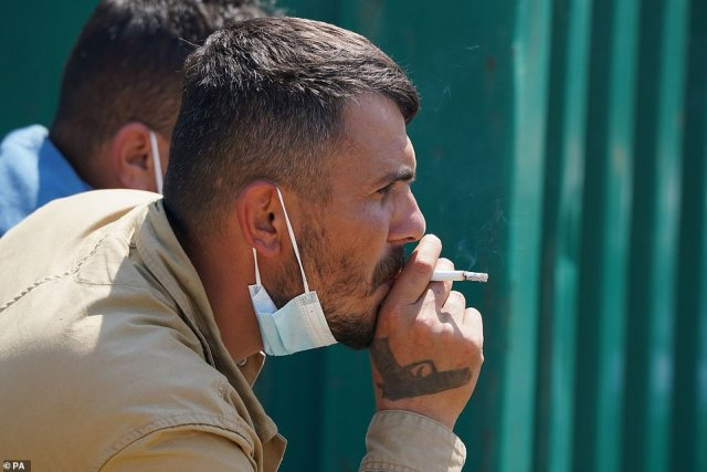 A man thought to be migrant smokes a cigarette after being escorted from the beach in Dungeness, Kent, by Border Force officers following a small boat incident in the Channel