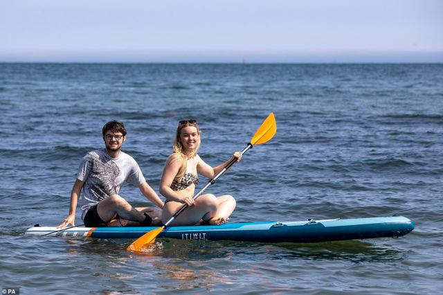 Aneurin Duffin-Murray (left) and Lauren Dalzell from Belfast on a paddle board at Helen's Bay beach in County Down, Northern Ireland