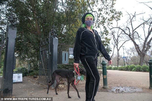 A woman is seen walking her dog in Melbourne on Tuesday. Victoria is in the midst of its fifth lockdown