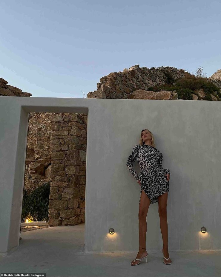 I call this place home... for now: This weekend she was seen in a black and white leopard print mini dress with sandal heels in silver at sunset at her stunning white hotel hut