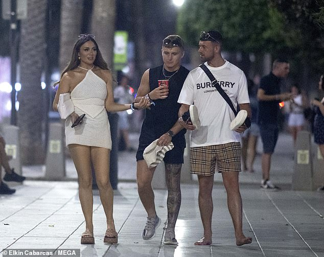 Wild:Frankie Sims enjoyed a boozy night out with two male companions in Ibiza on Tuesday, with one even appearing to get her name tattooed on his leg after leaving the club