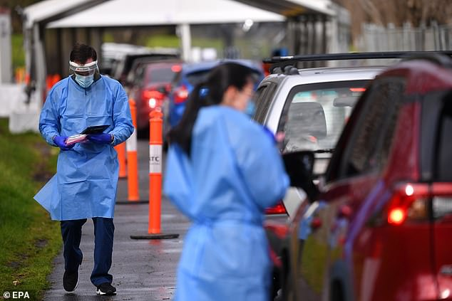 Health care workers are seen at a drive-through testing clinic in Melbourne on Wednesday