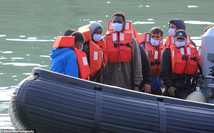 A group of migrants wearing lifejackets and facemasks are taken ashore to Dover Marina in Kent yesterday