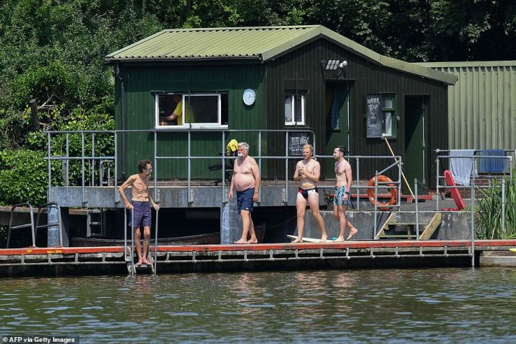 A swimmer walk to the water at the men's bathing pond in Hampstead Heath in North London this morning