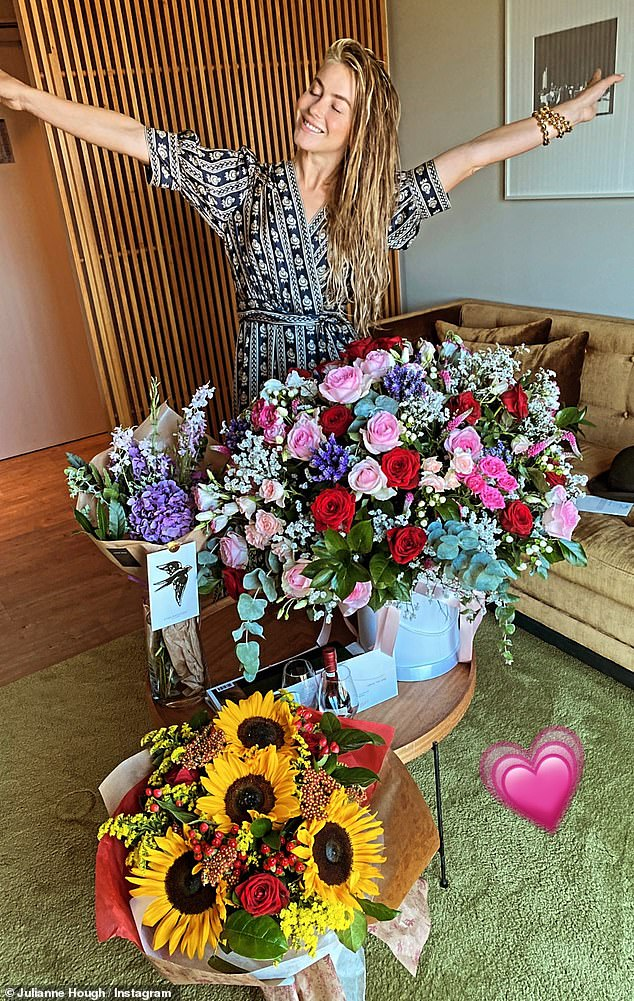 Colorful displays: The dancer also shared an image of herself standing in front of a set of beautiful flower arrangements