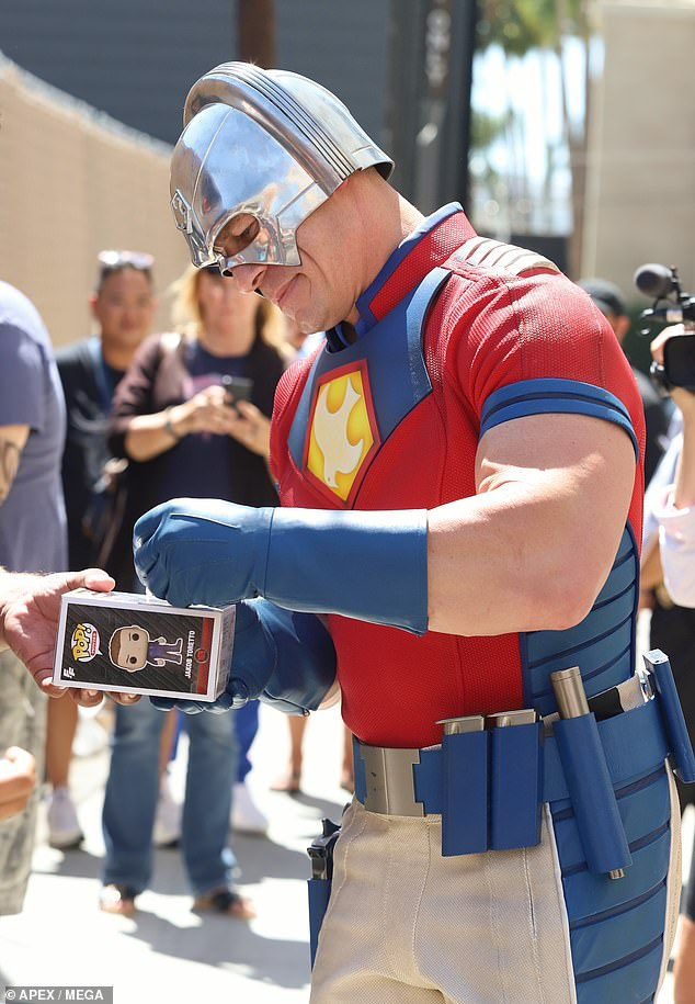 Autographs:Cena was spotted in the rear entrance to the Jimmy Kimmel Live studio signing various items for fans in his full suit, which includes a shiny silver helmet