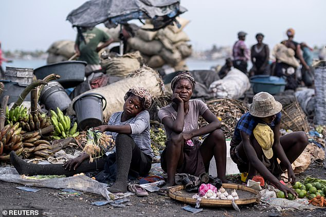 People with fresh produce look on at a market in Cap-Haitien as violence spreads ahead of the funeral of PresidentMoise