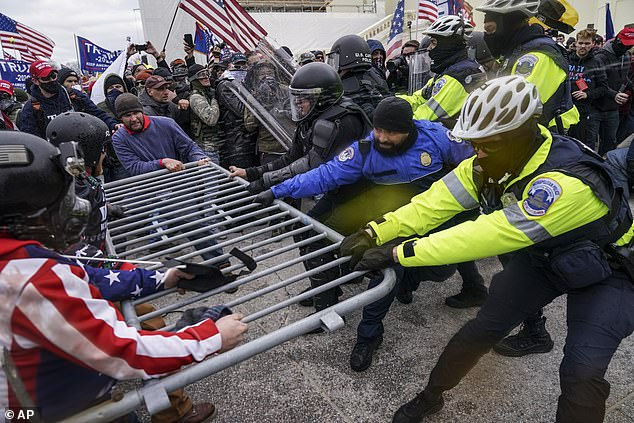 Rioters cross a police barrier near the Capitol on Jan. 6.  Trump claimed crowd was 'led into Capitol' by police officers 'hug and kiss' them