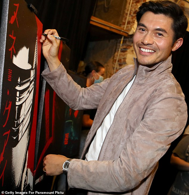 Beaming: He flashed his megawatt smile for the cameras as he signed one of the posters for the film to be released on Friday