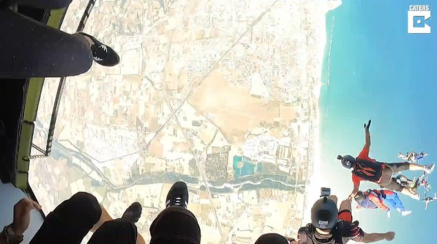 Footage shows veteran and daredevil Mr Vajeika confidently jumping out of the plane to join the others in the stunt